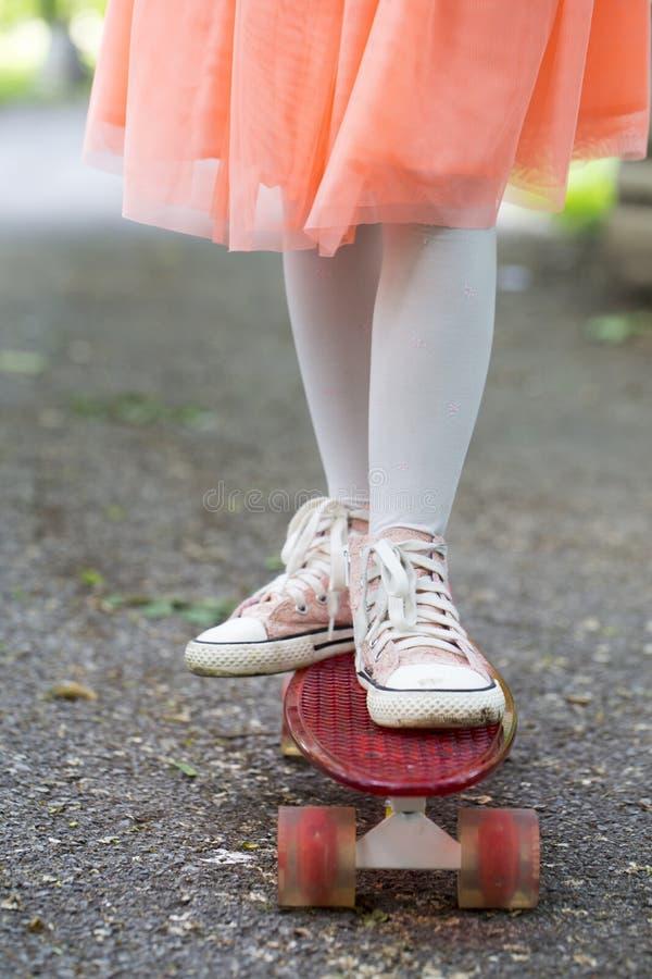 Niña en una falda que monta un paseo del monopatín en el parque fotos de archivo