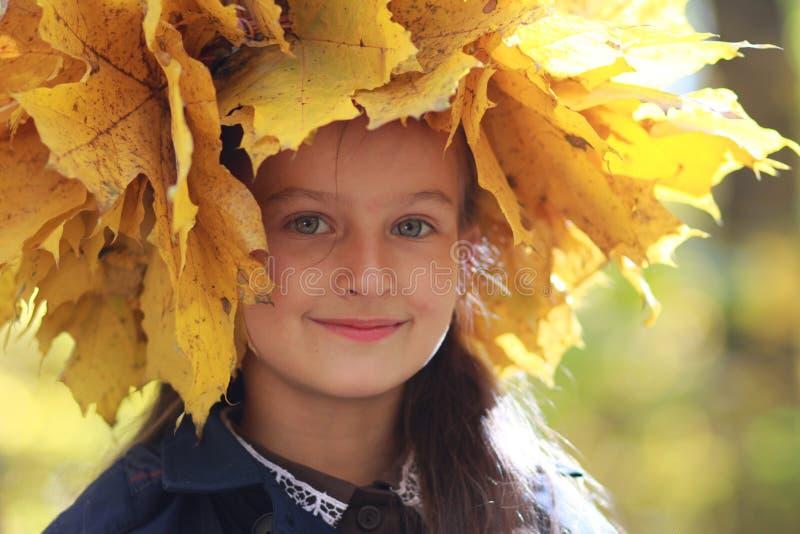 Niña en una guirnalda de las hojas de otoño amarillas imagenes de archivo