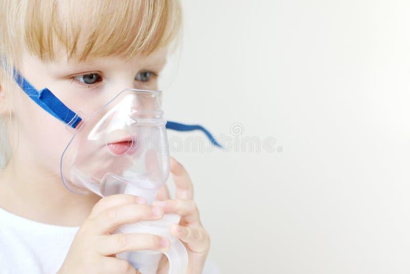 Niña en una máscara para las inhalaciones, haciendo la inhalación con el inhalador del nebulizador en casa en la tabla fotografía de archivo