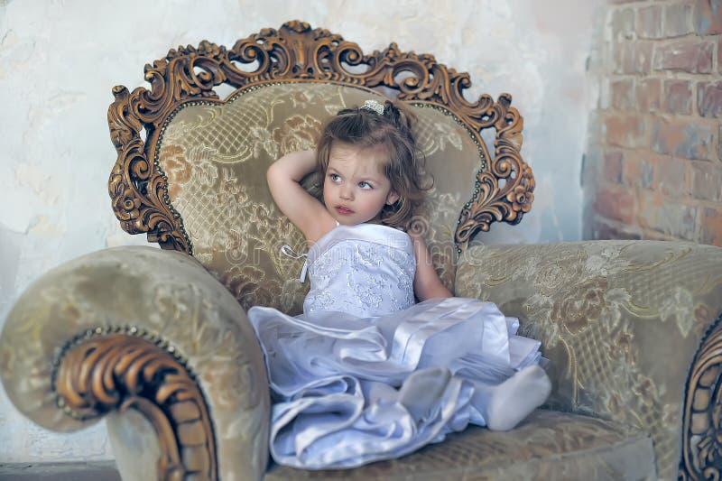 Niña en una silla antigua grande fotografía de archivo