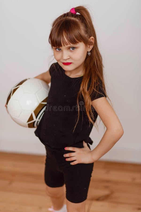 Niña en uniforme negro con un balón de fútbol foto de archivo libre de regalías