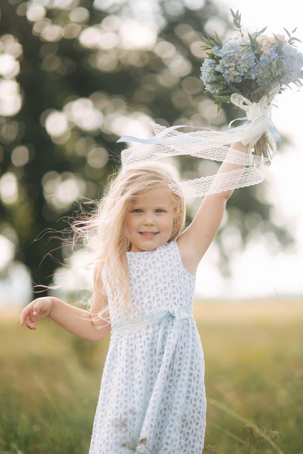 Niña en vestido del azul de cielo con el soporte del ramo en campo delante del árbol grande La sonrisa del niño y se divierte fotografía de archivo