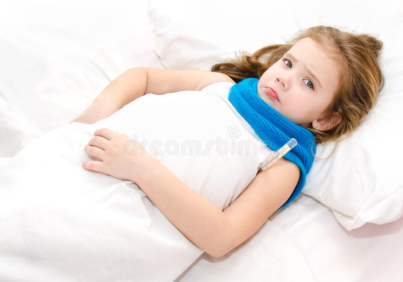 Niña enferma que miente en la cama foto de archivo