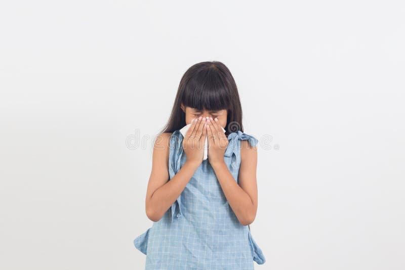 Niña enferma que sopla su nariz aislada en blanco fotografía de archivo libre de regalías