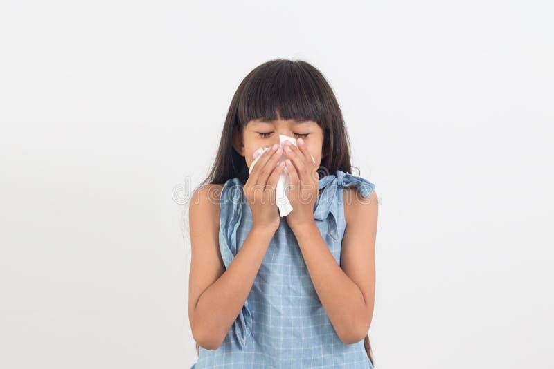 Niña enferma que sopla su nariz aislada en blanco fotografía de archivo