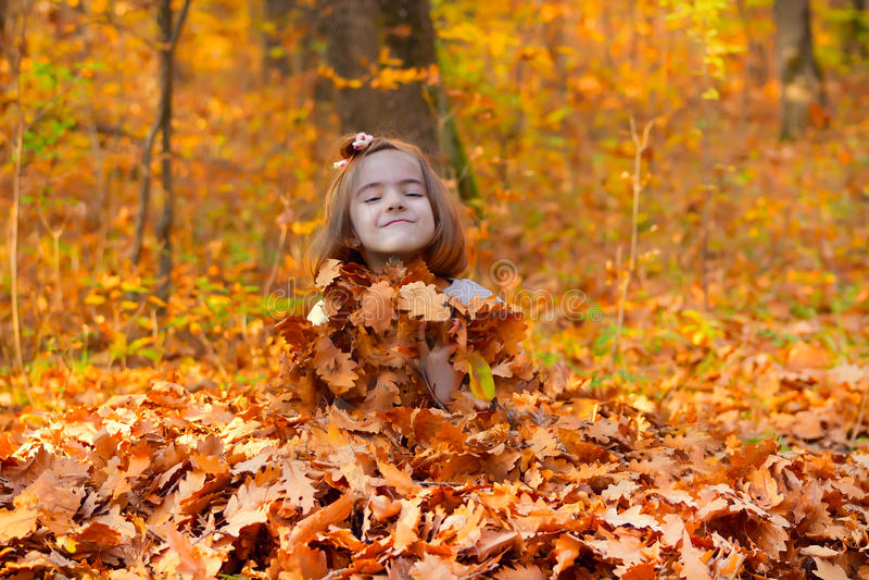 Niña enterrada en hojas de la caída fotos de archivo