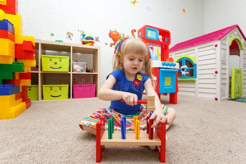 Niña fascinada que juega con el martillo de madera en kindergarte foto de archivo libre de regalías