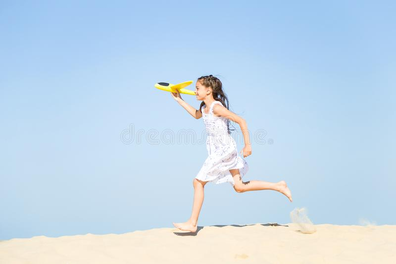 Niña feliz adorable que lleva un vestido blanco que corre en la playa arenosa por el mar y que juega con la y fotos de archivo