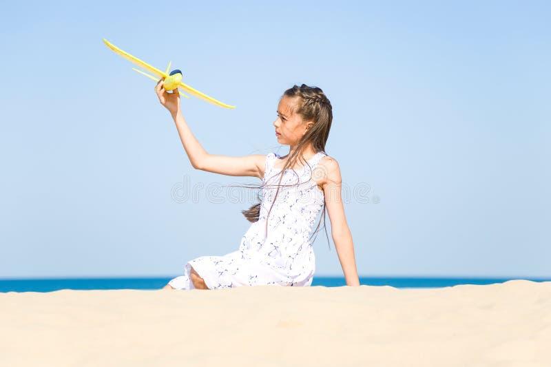 Niña feliz adorable que lleva un vestido blanco que se sienta en la playa arenosa por el mar y que juega con la y imágenes de archivo libres de regalías