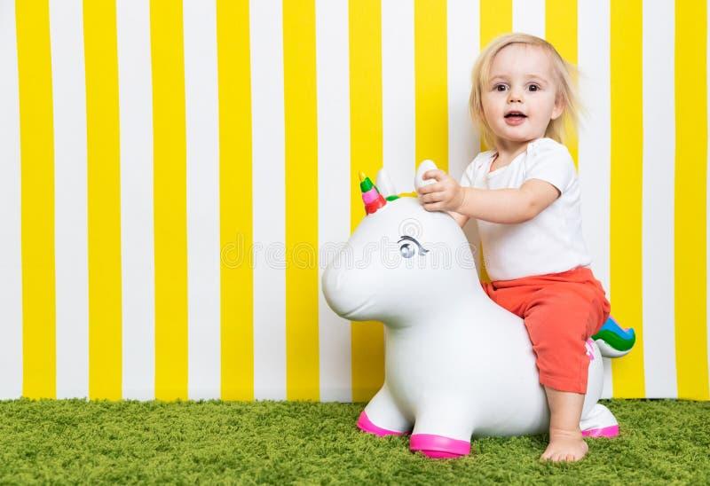 Niña feliz brillante en Toy Unicorn Niñez Fondo imagen de archivo libre de regalías