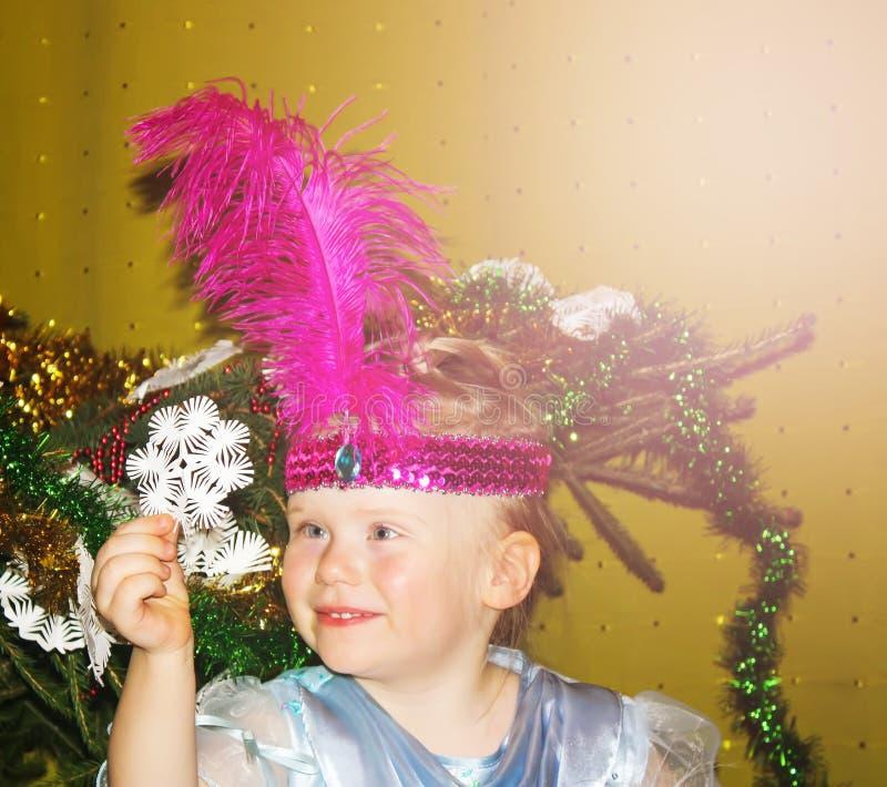 Niña feliz con el copo de nieve del Libro Blanco cerca del árbol del Año Nuevo imagen de archivo