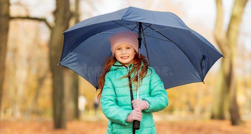 Niña feliz con el paraguas en el parque del otoño fotos de archivo