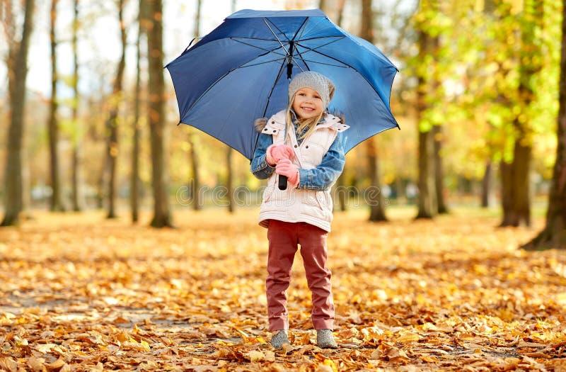 Niña feliz con el paraguas en el parque del otoño foto de archivo