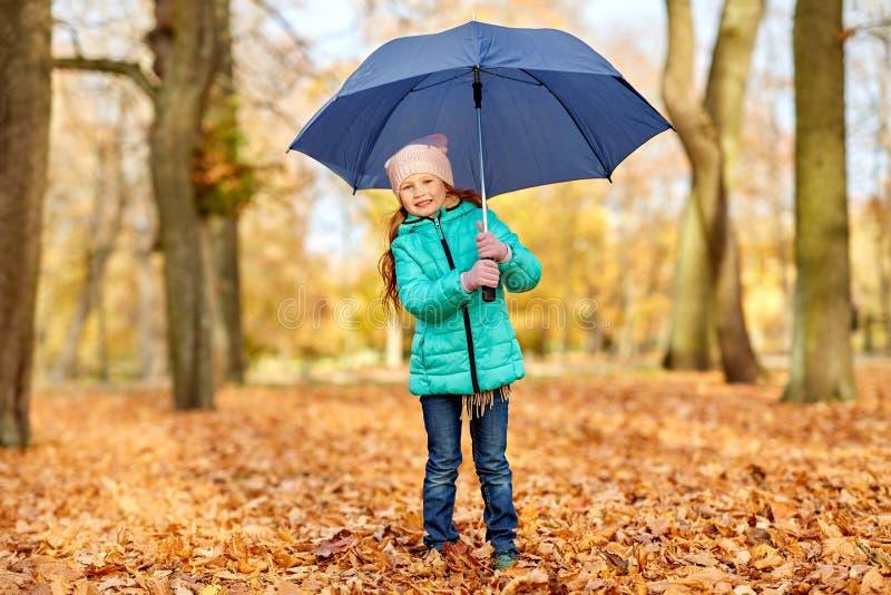 Niña feliz con el paraguas en el parque del otoño foto de archivo libre de regalías