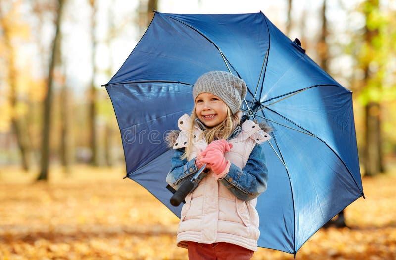 Niña feliz con el paraguas en el parque del otoño imagenes de archivo