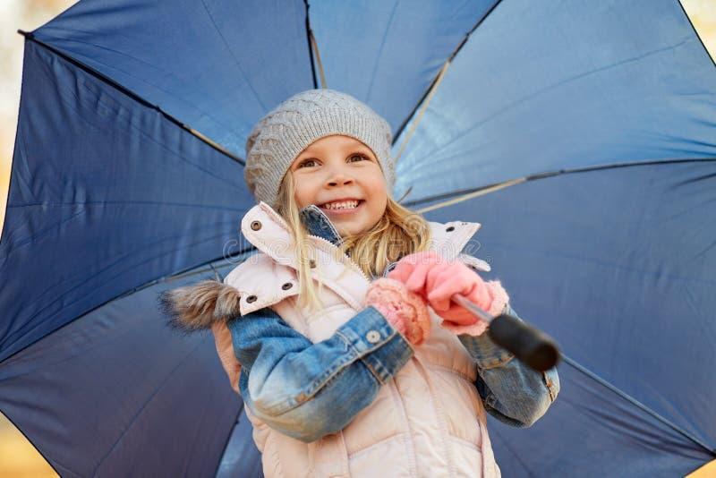 Niña feliz con el paraguas en el parque del otoño fotografía de archivo