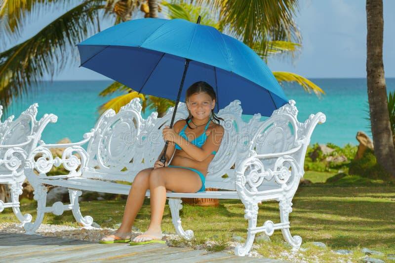 Niña feliz con el paraguas, sentándose en banco del metal del viejo estilo imagenes de archivo