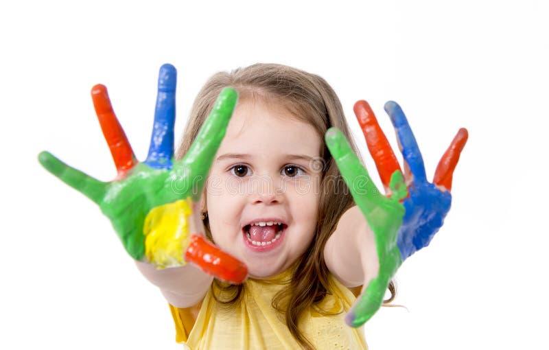 Niña feliz con las manos pintadas en color imagen de archivo