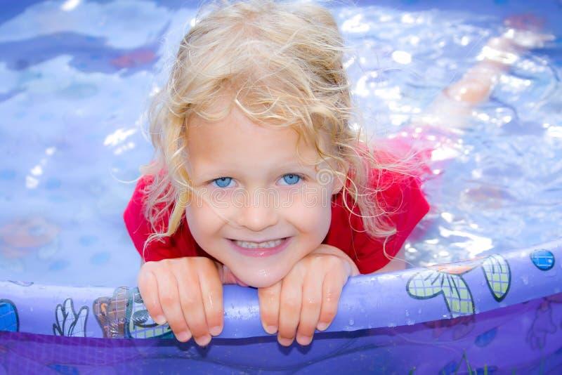 Niña feliz con los ojos azules en una piscina. foto de archivo