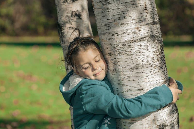 Niña feliz con los ojos cerrados, abrazando árboles de un abedul en parque del otoño y disfrutando de su tiempo libre en día cali imágenes de archivo libres de regalías