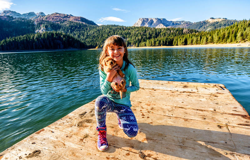 Niña feliz con un perrito por el lago negro (jezero de Crno), foto de archivo