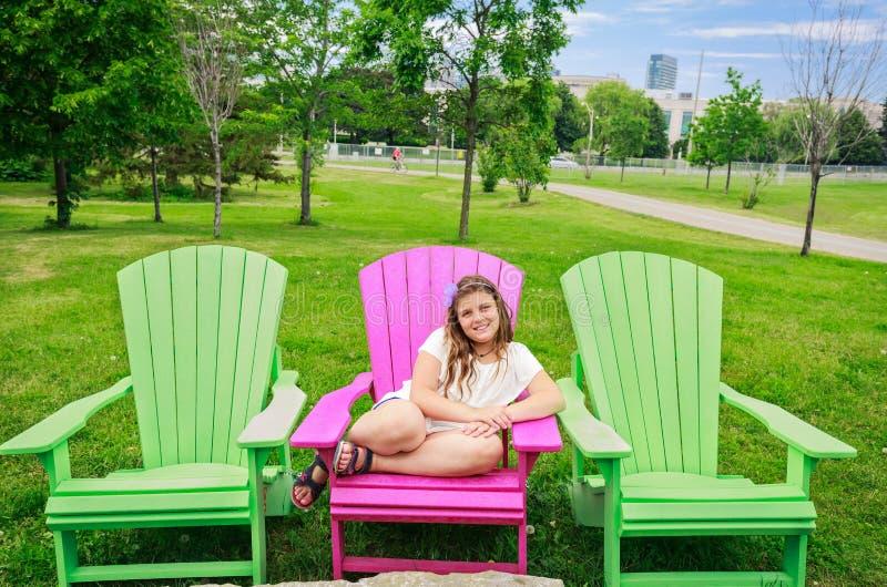 Niña feliz de la sonrisa que se sienta en silla cómoda rosada y que disfruta de su tiempo libre imagen de archivo libre de regalías