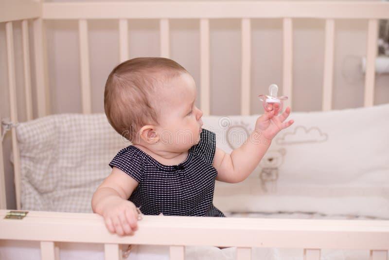 Niña feliz del bebé que juega con un pacificador en su cama, en casa imagen de archivo libre de regalías