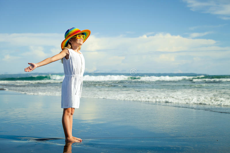 Niña feliz en el sombrero que se coloca en la playa en el día t fotos de archivo libres de regalías