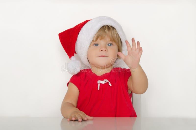 Niña feliz en el traje de Papá Noel en la tabla foto de archivo libre de regalías