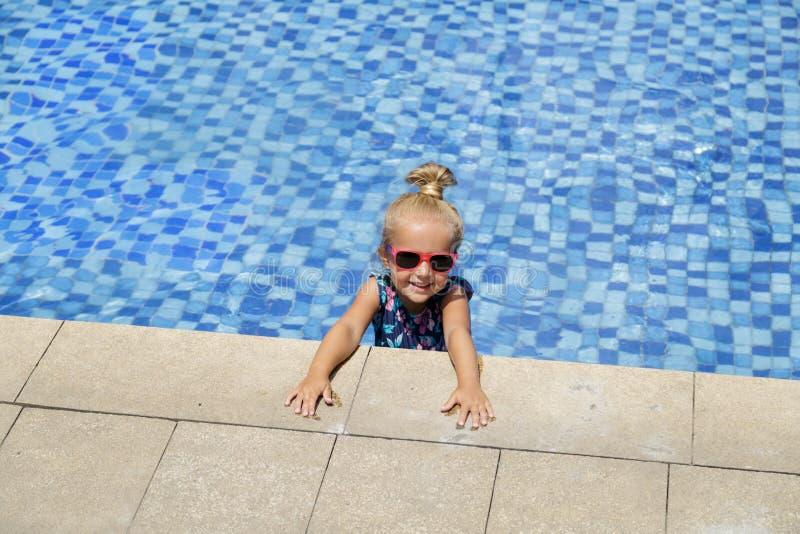 Niña feliz en piscina al aire libre en día de verano caliente Los ni?os aprenden nadar Juego de ni?os en centro tur?stico tropica fotos de archivo