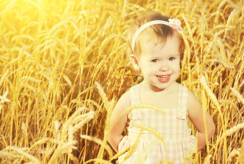 Niña feliz en un campo del trigo de oro en verano imágenes de archivo libres de regalías
