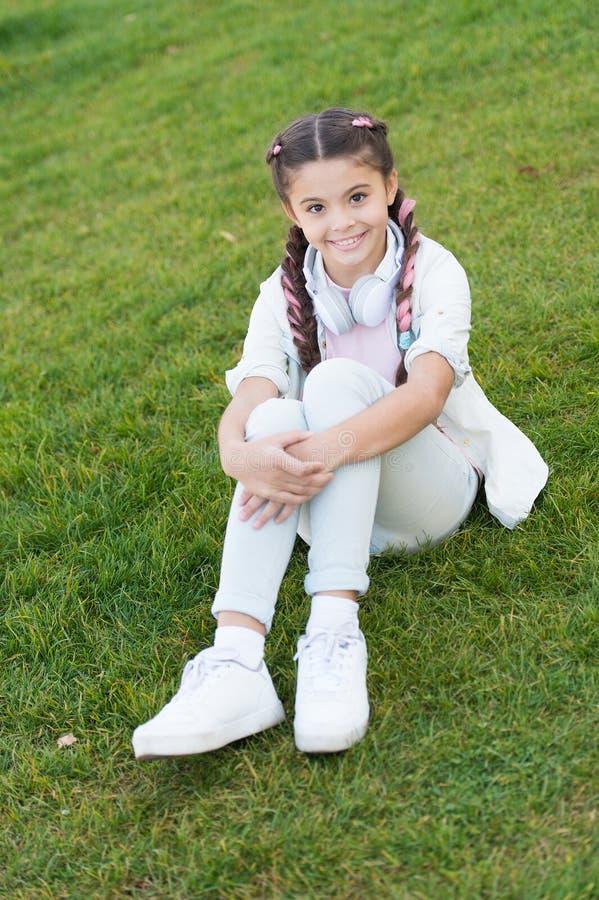 Niña feliz Libro audio Humor del resorte Jugador Mp3 [1] Niño en auriculares La niña escucha música El niño elegante se relaja foto de archivo libre de regalías