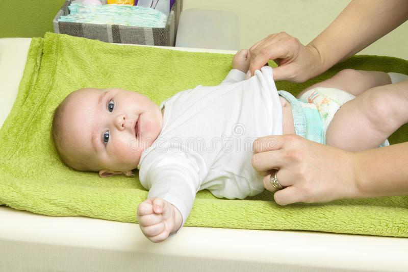Niña feliz linda que consigue vestida Madre que viste a su bebé en el cojín cambiante Bebé infantil con el pañal imagenes de archivo