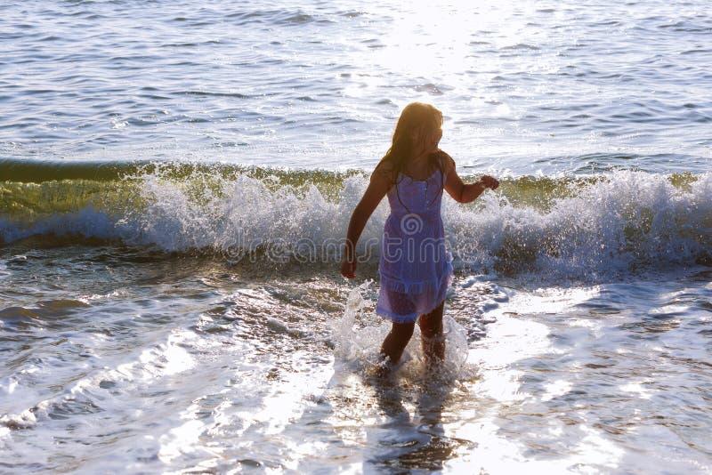 Niña feliz linda que corre a lo largo de la playa en el salto sobre ondas Día soleado hermoso del verano, mar azul, paisaje pinto imágenes de archivo libres de regalías