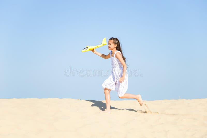 Niña feliz linda que lleva un vestido blanco que corre en la playa arenosa por el mar y que juega con el yello fotos de archivo