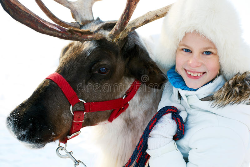 Niña feliz que abraza su reno imagen de archivo