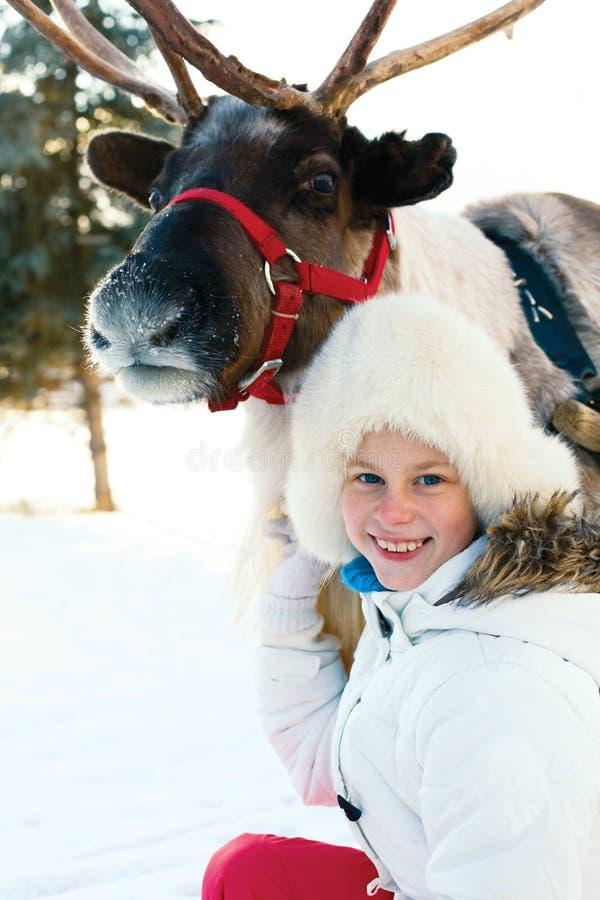 Niña feliz que abraza su reno Hora del recreo del invierno imagen de archivo