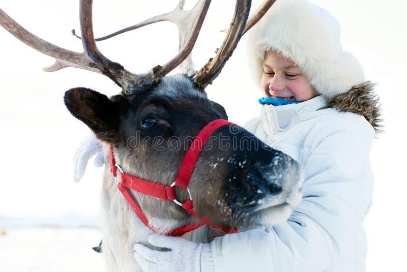 Niña feliz que abraza su reno Hora del recreo del invierno foto de archivo