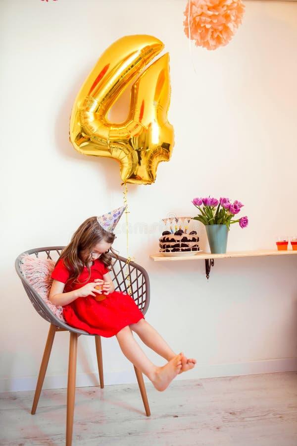 Niña feliz que celebra el cuarto cumpleaños en casa fotos de archivo libres de regalías
