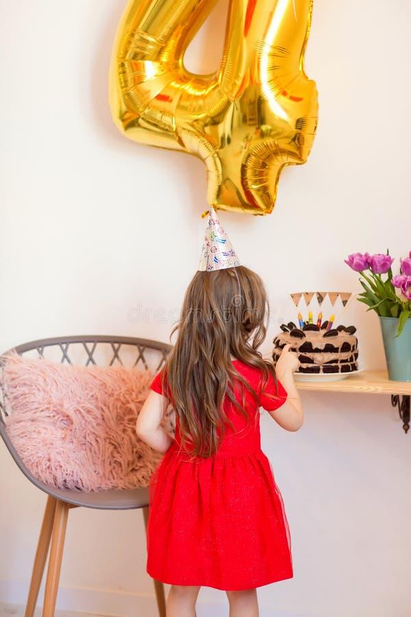 Niña feliz que celebra el cuarto cumpleaños en casa imagenes de archivo