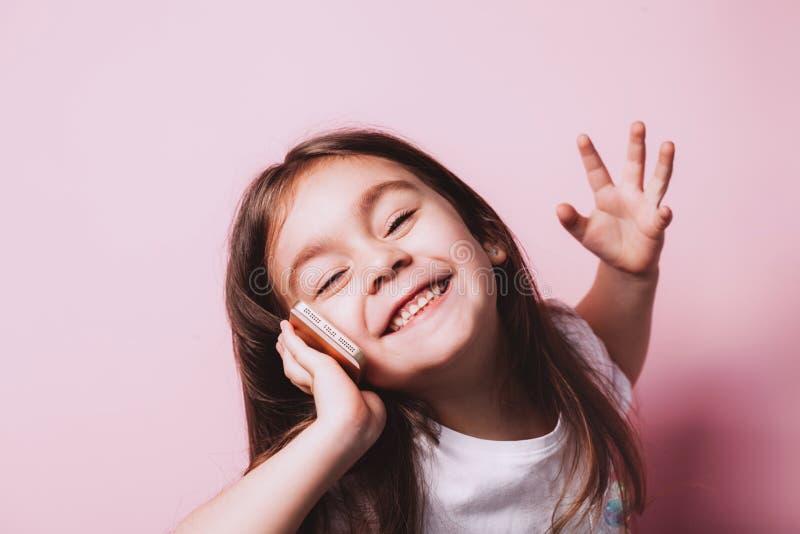 Ni?a feliz que habla en el tel?fono en fondo rosado imagen de archivo libre de regalías