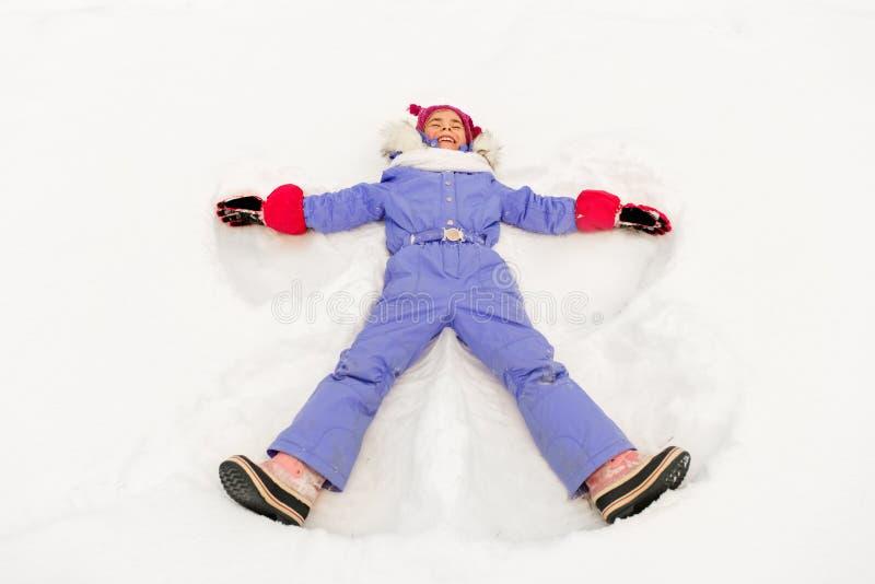 Niña feliz que hace ángeles de la nieve en invierno imagenes de archivo
