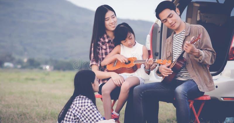 Niña feliz que juega el ukelele con la familia asiática que se sienta en t imagenes de archivo