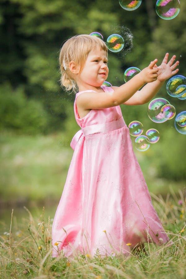 Niña feliz que persigue burbujas en la naturaleza en el parque imagen de archivo