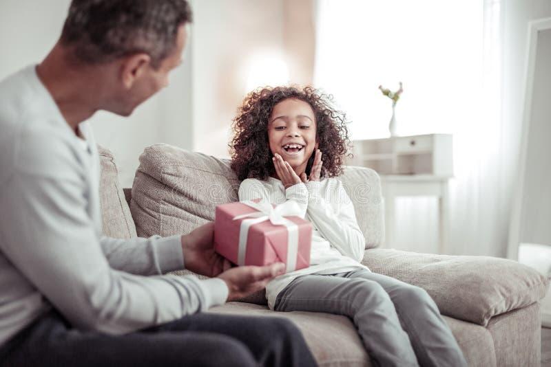 Niña feliz que recibe un bonito regalo de su padre imagen de archivo libre de regalías