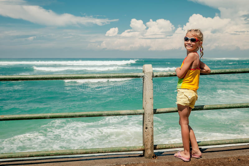 Niña feliz que se coloca en la playa imagen de archivo