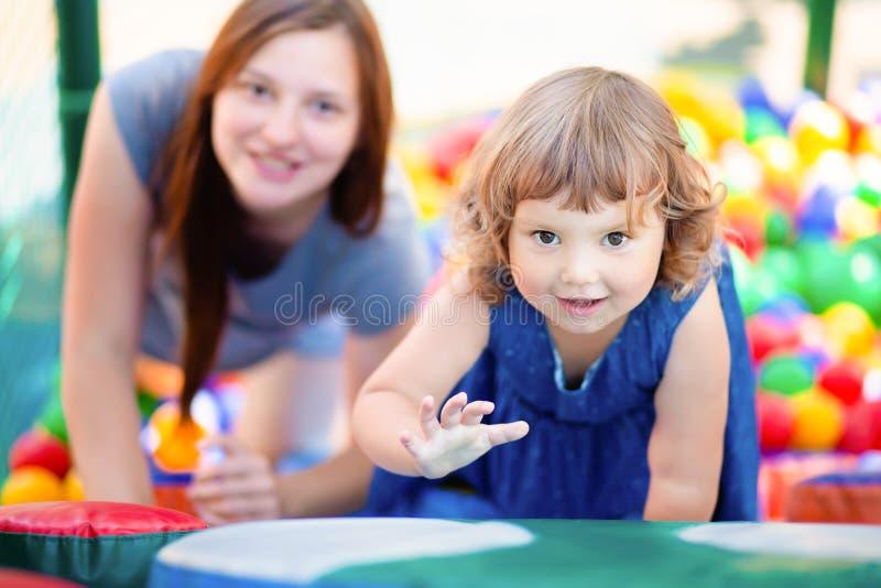 Ni?a feliz que se divierte en piscina pl?stica colorida de las bolas con su madre imágenes de archivo libres de regalías