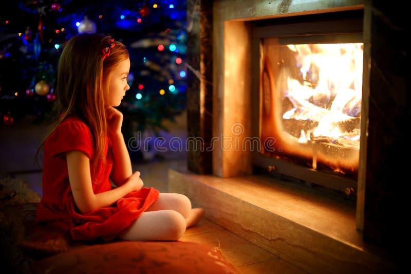 Niña feliz que se sienta por una chimenea el Nochebuena imagen de archivo