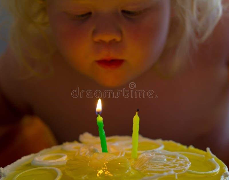 Niña feliz que sopla hacia fuera velas en una torta en su cumpleaños foto de archivo