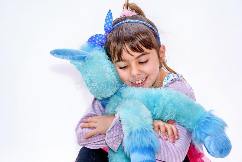 Niña feliz que sostiene el juguete azul del unicornio aislado en blanco fotos de archivo